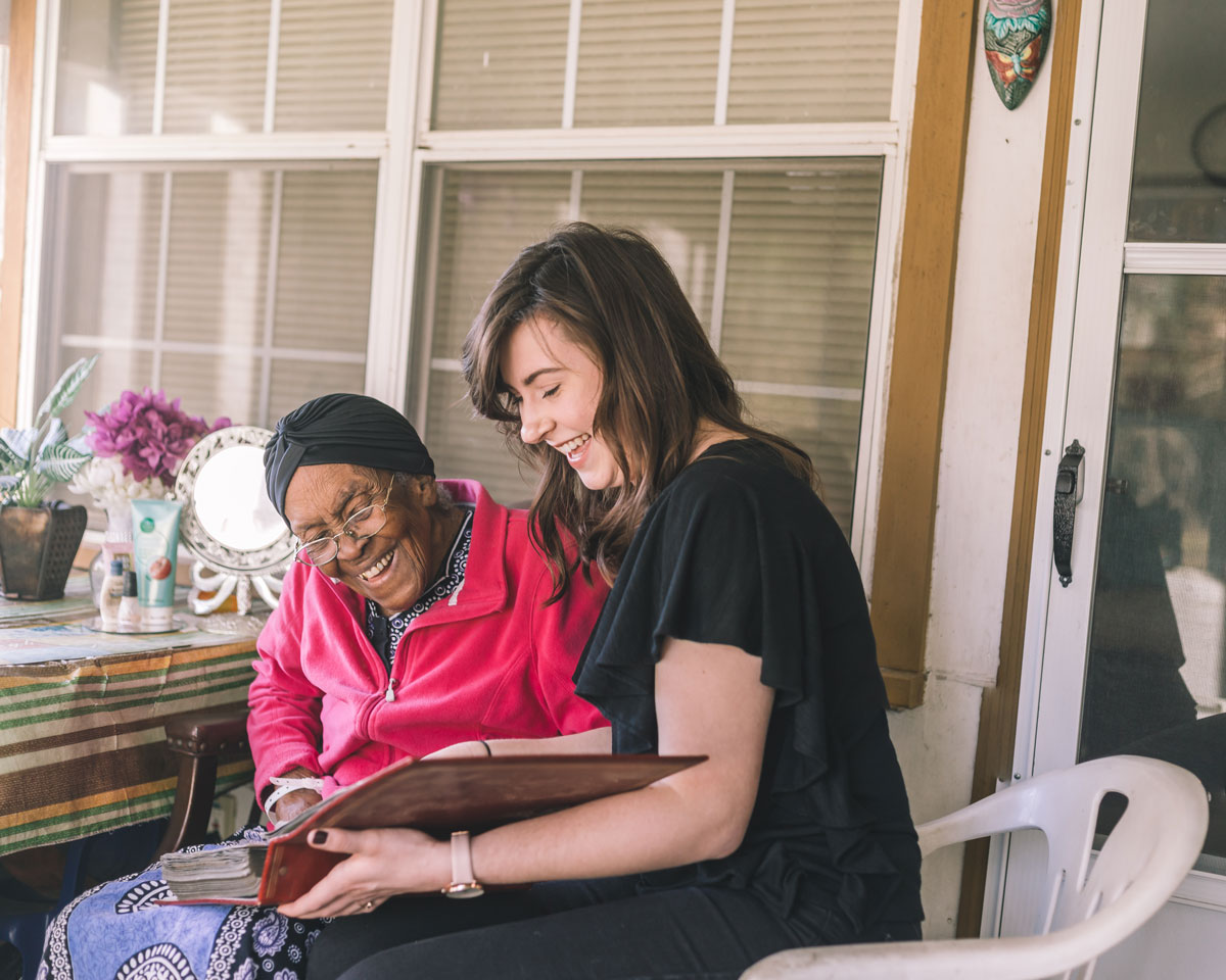 smiling volunteer looking over photo album with happy senior